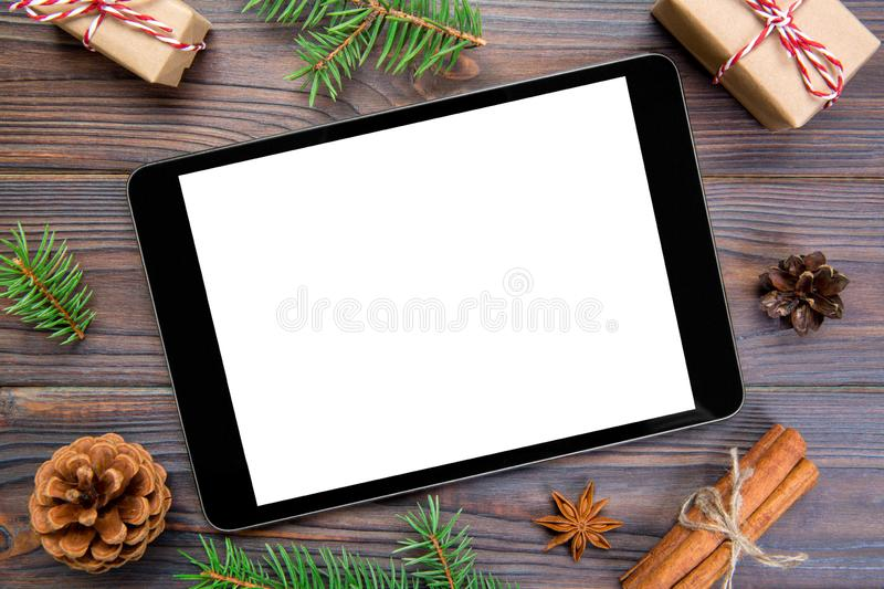 Digital tablet mock up with rustic Christmas wooden background decorations for app presentation. top view with copy space royalty free stock photography