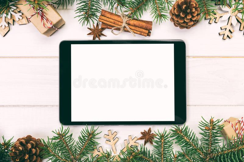 Digital tablet mock up with rustic Christmas wooden background decorations for app presentation. top view with copy space. Toned royalty free stock photography