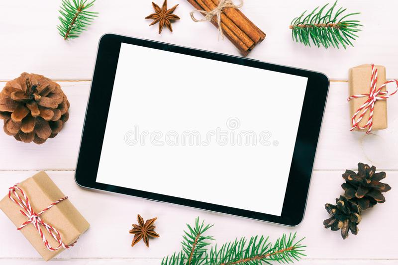 Digital tablet mock up with rustic Christmas wooden background decorations for app presentation. top view with copy space. Toned royalty free stock photo