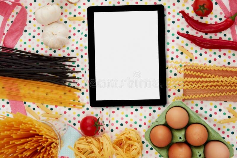 Digital tablet and pasta preparation stock photos