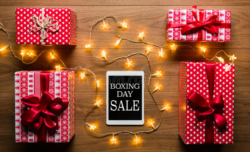 Digital tablet, presents and christmas lights, retro Boxing Day Sale concept royalty free stock image