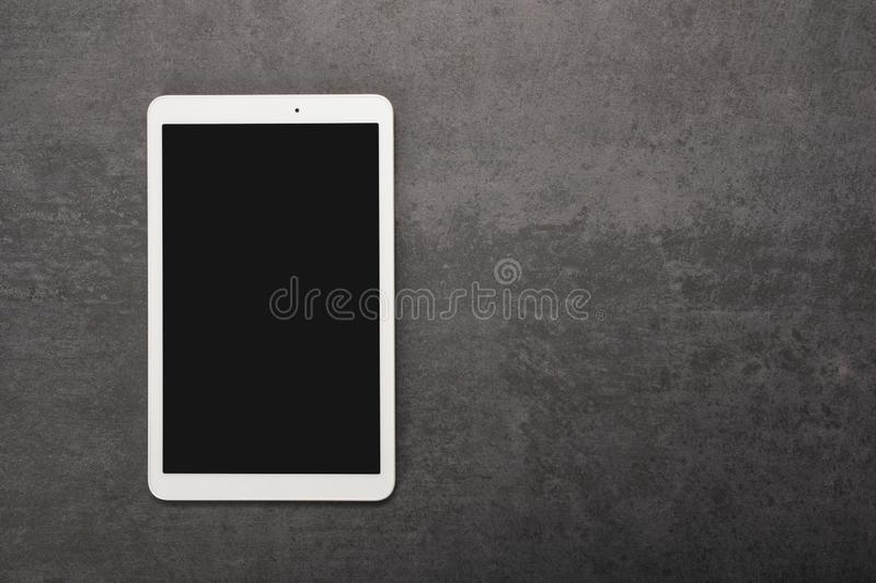 Digital tablet screen has clipping path on gray stone background with copy space royalty free stock images