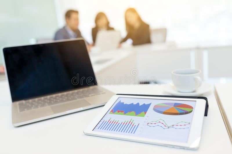 Digital tablet showing data chart on screen and blank screen of. Laptop computer at business meeting room royalty free stock image