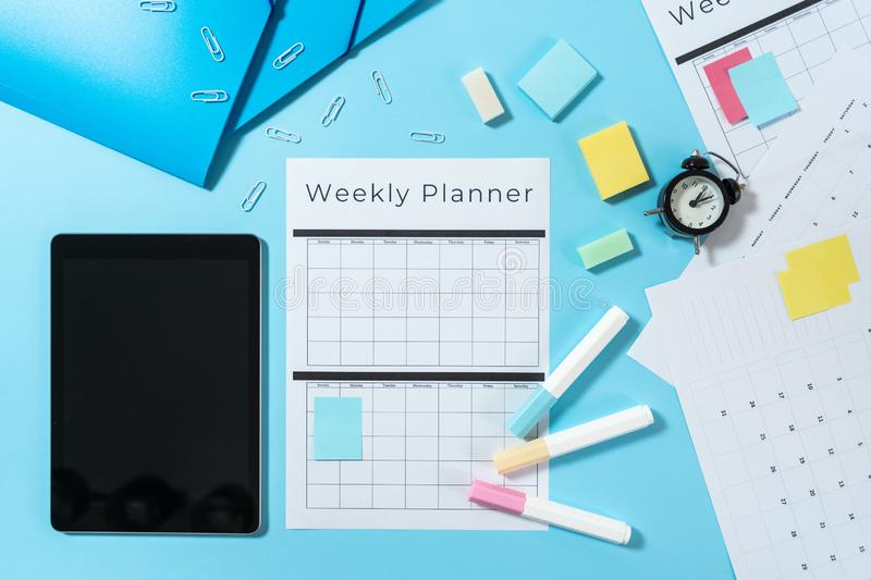 Digital tablet, stationery and planner on blue pastel background royalty free stock photography