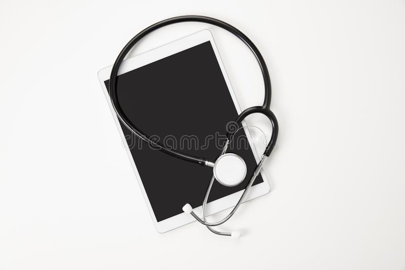 Digital Tablet And Stethoscope On White Table stock photos