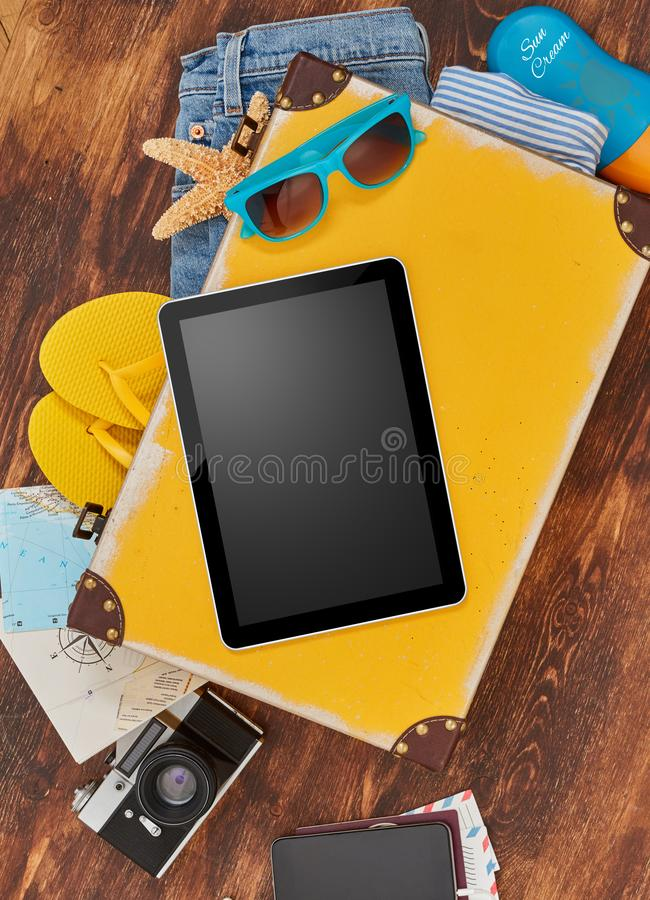 Digital tablet and suitcase royalty free stock photography