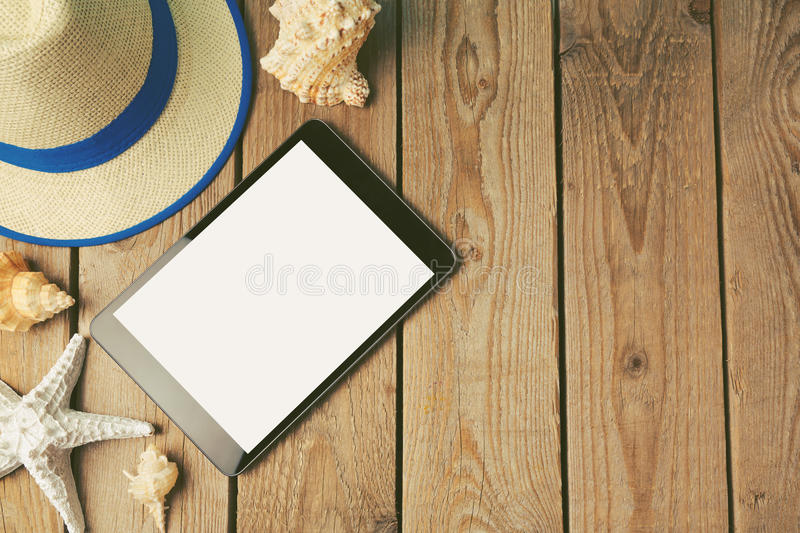 Digital tablet, summer hat and seashells on wooden background royalty free stock photos
