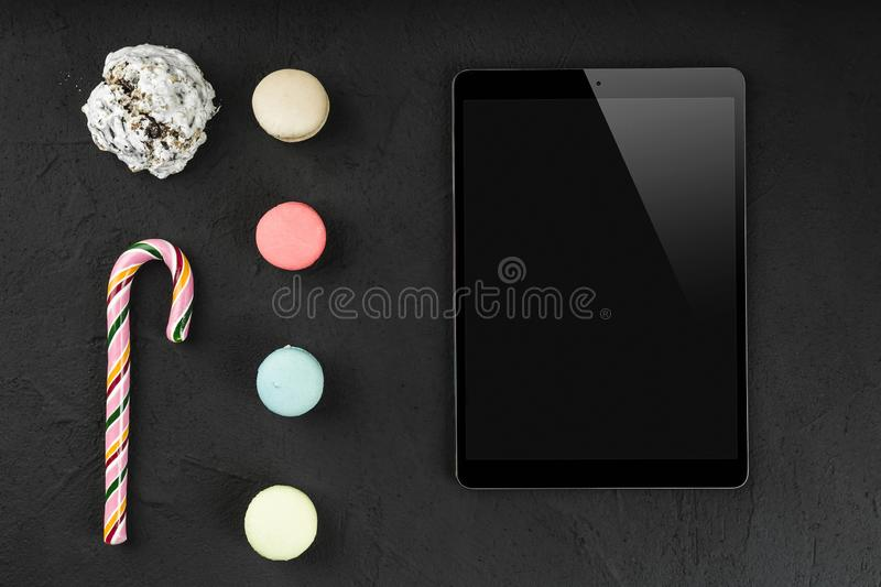 Digital tablet with sweet macarons, lollipop and biscuit on stone background. Copy space, flat lay stock photography