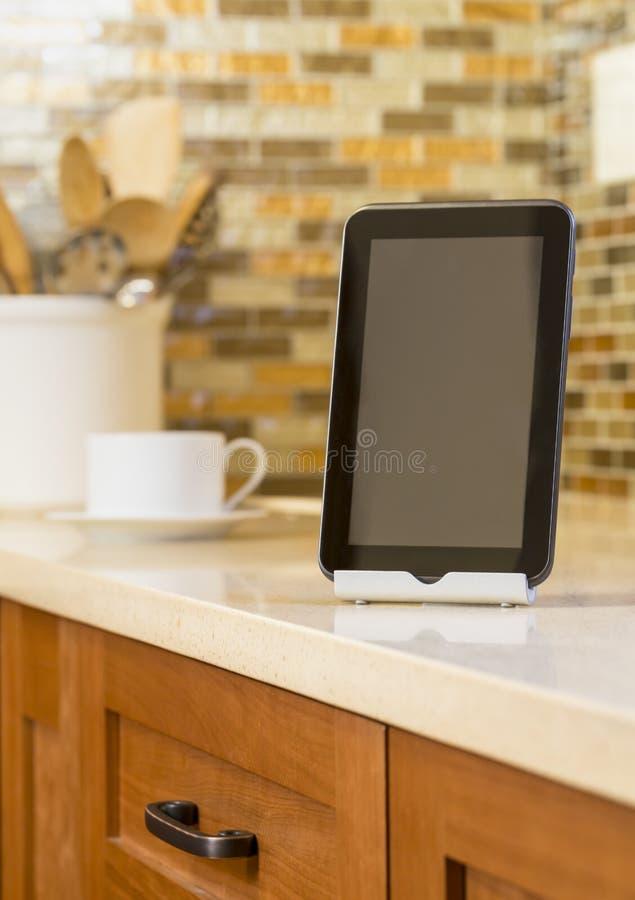 Digital-Tablette, die auf Zähler in einer zeitgenössischen, modernen Küche mit Kaffeetasse sitzen und Glas decken backsplash im H lizenzfreies stockbild