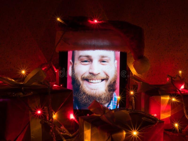 Digital-Tablette mit bärtigem Mann auf Schirm und Sankt-Kappe setzte an sie mit Weihnachtsgeschenken und Lampengirlande herum stockbild