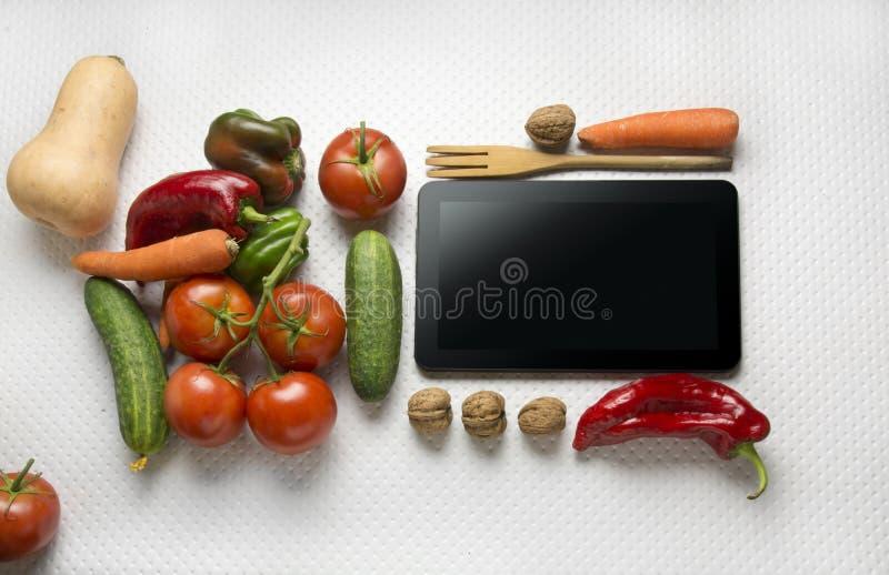 Digital-Tablette mit Frischgemüse lizenzfreie stockbilder