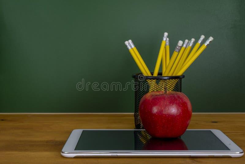 Digital-Tablette und -apfel auf dem Schreibtisch vor Tafel stockfotografie