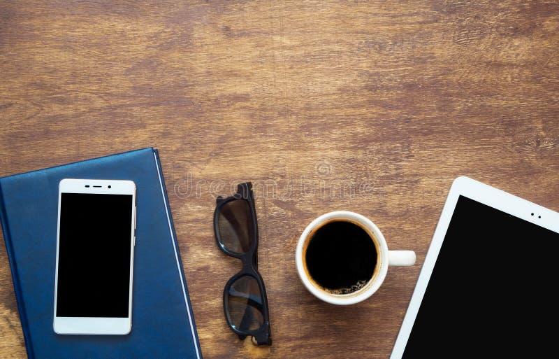 Digital-Tablette und -Tasse Kaffee auf hölzernem Schreibtisch Intelligentes Telefon auf Th stockbilder