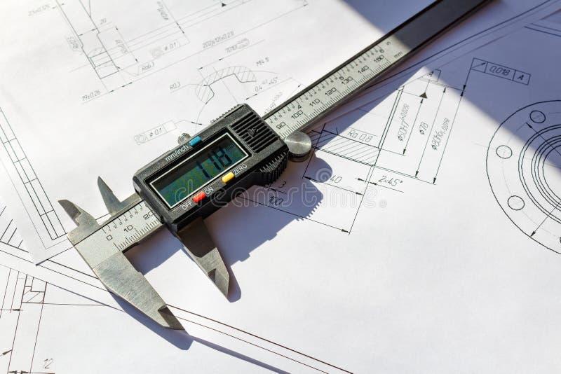 Digital-Tasterzirkel liegt auf technische Konstruktionszeichnungen stockbild