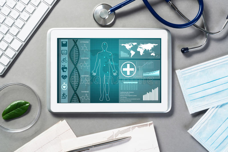 Digital technologies in medicine. White tablet pc and doctor tools on gray surface royalty free stock photos