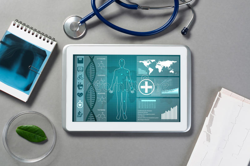 Digital technologies in medicine. White tablet pc and doctor tools on gray surface royalty free stock photo