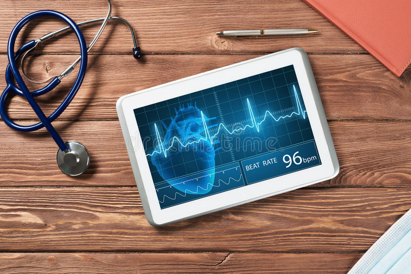 Digital technologies in medicine. White tablet pc and doctor tools on wooden table stock image