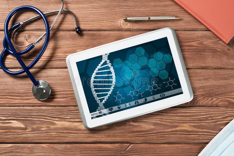 Digital technologies in medicine. White tablet pc and doctor tools on wooden table royalty free stock photos