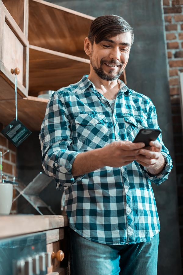 Happy delighted man using his device stock photos