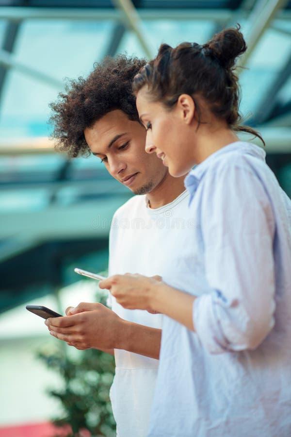 Digital teknologi och resande Unga ?lska par i tillf?lliga kl?der genom att anv?nda smartphonen, medan st? i flygplatsen royaltyfri bild