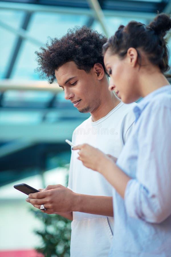 Digital teknologi och resande Unga ?lska par i tillf?lliga kl?der genom att anv?nda smartphonen, medan st? i flygplatsen arkivbild