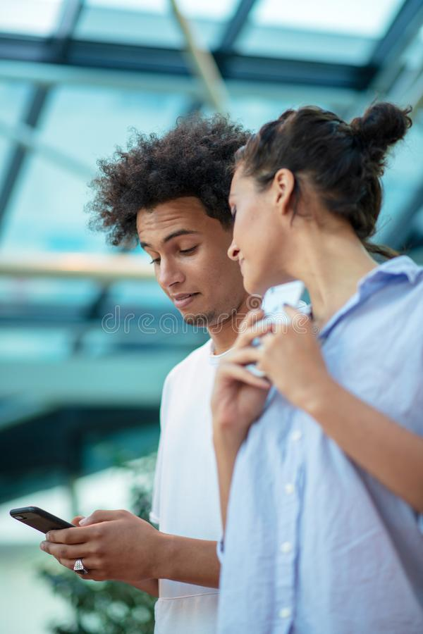 Digital teknologi och resande Unga ?lska par i tillf?lliga kl?der genom att anv?nda smartphonen, medan st? i flygplatsen arkivbilder