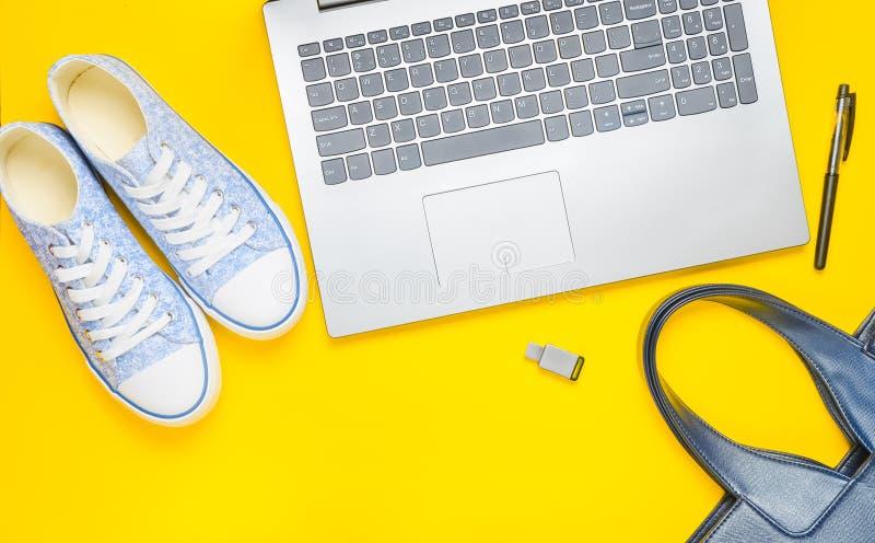 Digital teknologi och trendig women' s-tillbehör på en gul bakgrund: bärbar dator pråligt drev för usb, påse, plånbok, gymna royaltyfri bild