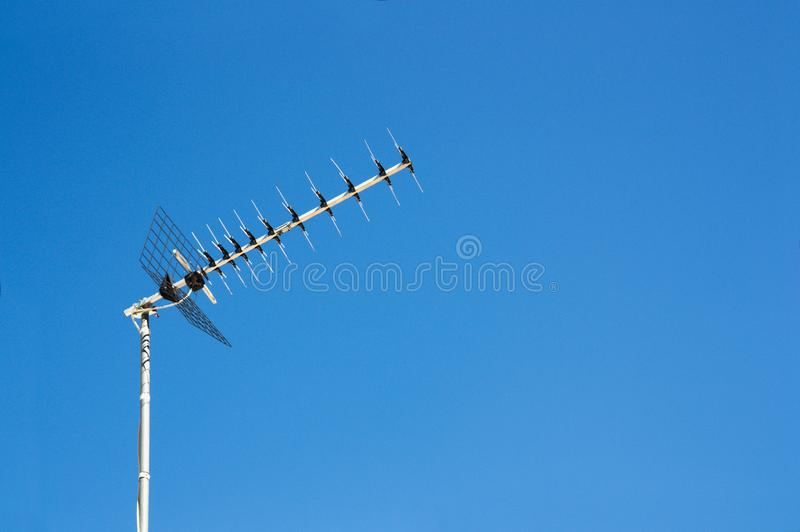 Digital terrestrial television reception antenna of a conventional house. Image of a television receiving antenna with the blue of the sky as background and royalty free stock image