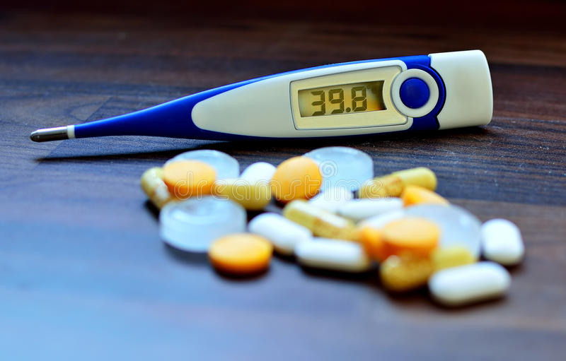 Digital thermometer and pills royalty free stock photo