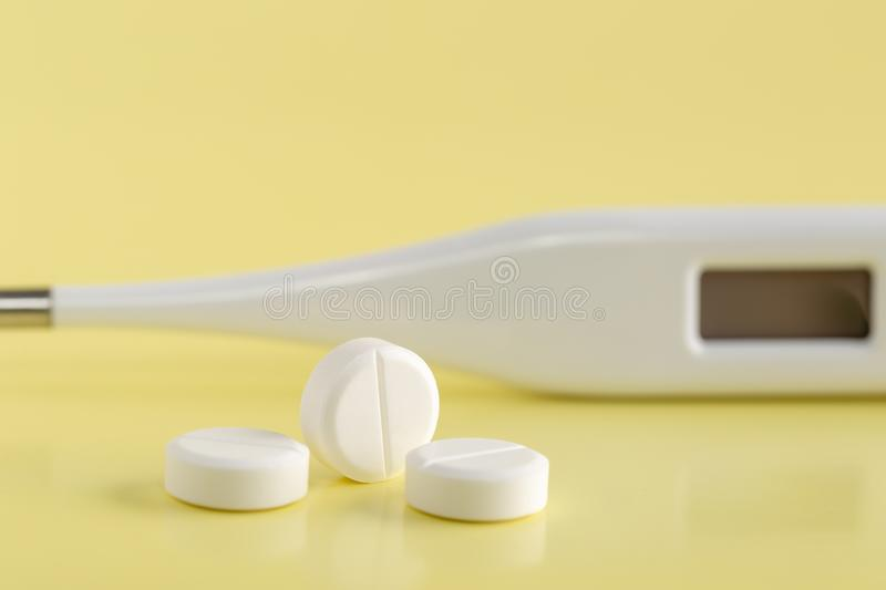 Digital thermometer and round white pills stock image