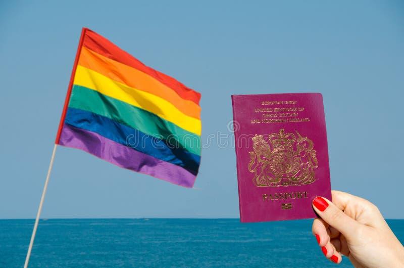 Digital-Zusammensetzung von LGBT-Flagge lokalisierte die Unterlassung des Ozeans mit der Hand, die BRITISCHEN Pass hält stockfoto