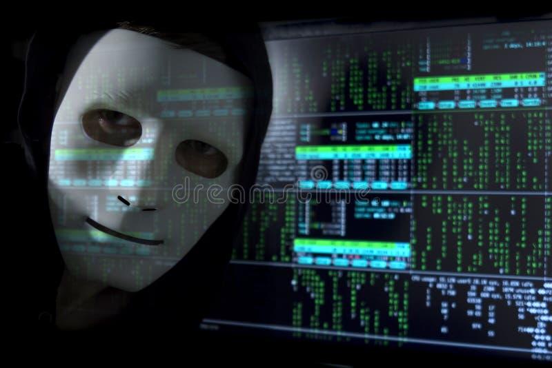 Digitala Blure Enen hacker i en maskering på bakgrunden av den binära koden royaltyfria bilder