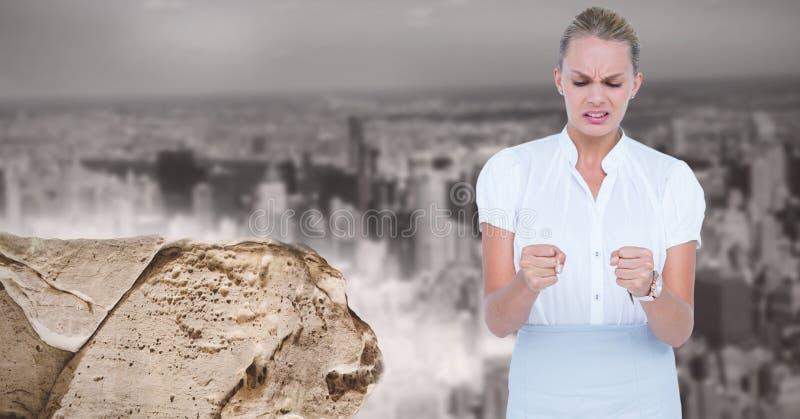 Digitalbild des bereitstehenden Felsens der verärgerten Geschäftsfrau gegen Stadt stockfotografie