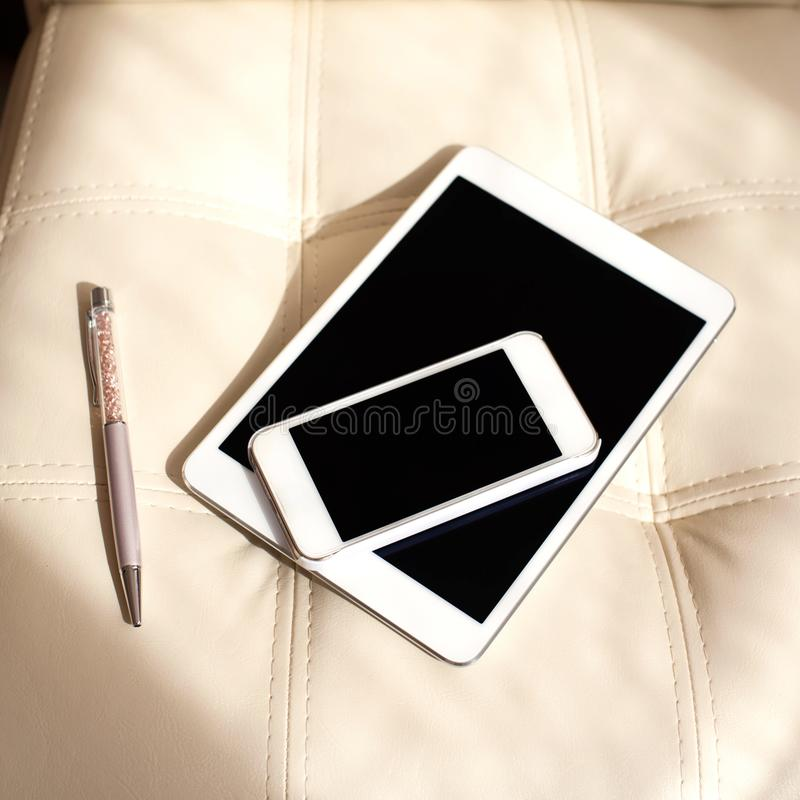 Digitale apparaten - witte smartphone en tablet op leerarmchai stock foto's