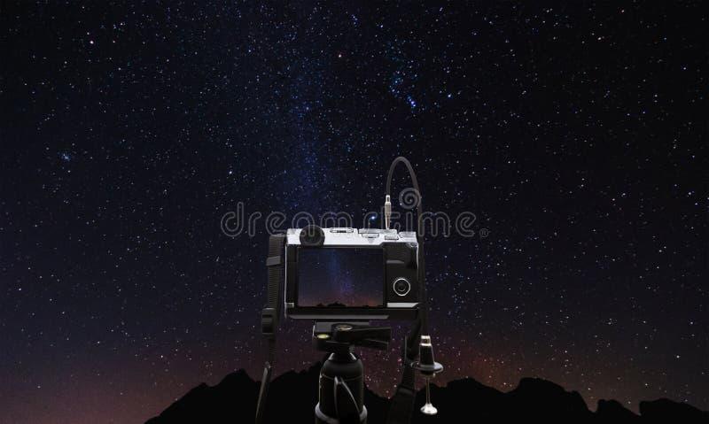 Digitale camera op cameradriepoot die een foto van melkachtige manier nemen bij nacht, met duidelijk hemelhoogtepunt van ster royalty-vrije stock afbeelding