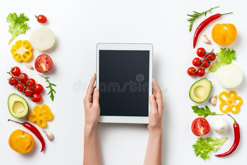 Digitale die tablet in vrouwenhanden en kruiden en groenten op witte achtergrond worden geïsoleerd De ruimte van het exemplaar royalty-vrije stock afbeeldingen