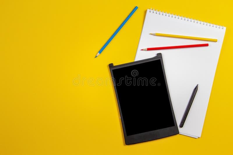 Digitale grafische tablet, kleurpotloden, Witboeknotitieboekje op gele achtergrond royalty-vrije stock afbeeldingen