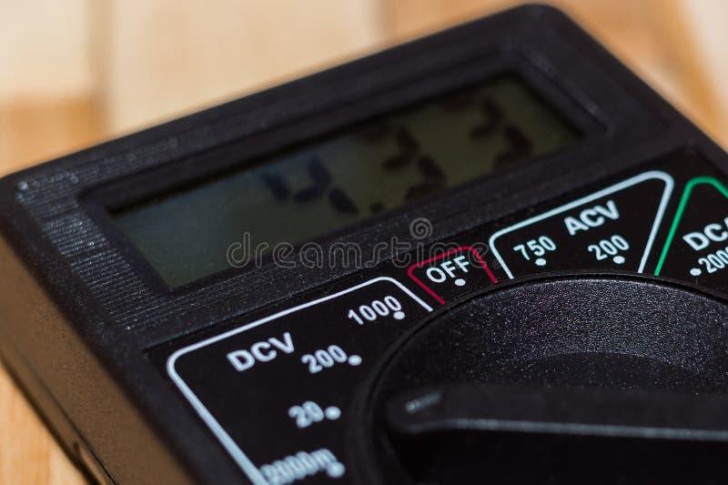 Digitale metende multimeter op houten vloer Het toont 4 33V of volledig geladen batterij Omvat voltmeter, ampermeter, ohmmeter royalty-vrije stock fotografie
