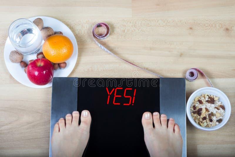 Digitale schalen met vrouwelijke voeten op hen en teken ` ja! ` door gezond voedsel wordt omringd dat stock foto's