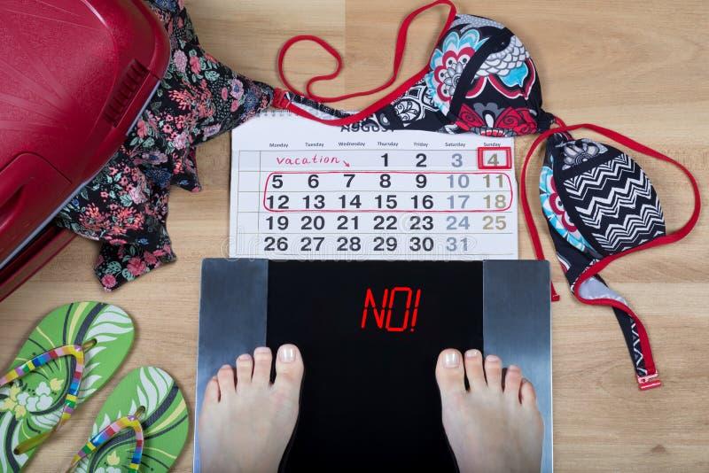 Digitale schalen met vrouwelijke voeten op hen en teken ` nr! ` door kalender en de zomervakantietoebehoren die wordt omringd stock foto's