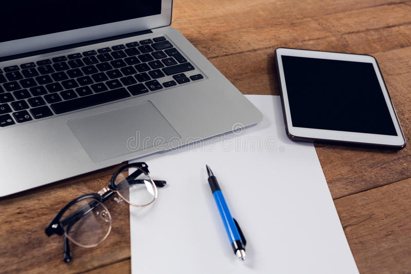 Digitale tablet, laptop, document, pen en bril op houten lijst stock foto's