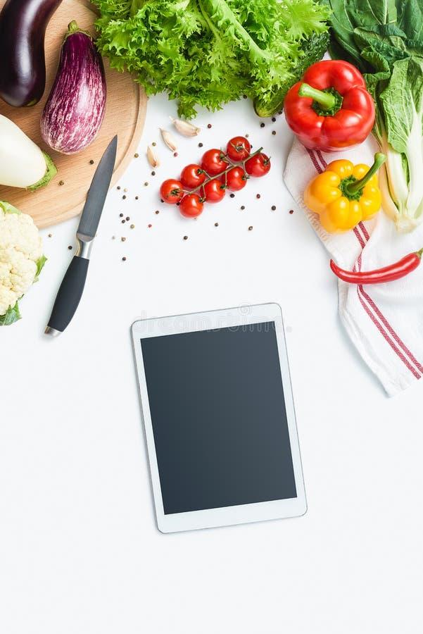Digitale tablet, mes, scherpe raad, kruiden en groenten op witte achtergrond De ruimte van het exemplaar royalty-vrije stock foto's