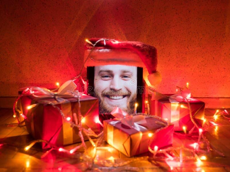 Digitale tablet met de gelukkige gebaarde mens op het scherm en santa GLB op het met Kerstmis rond giften en lichten stock foto's