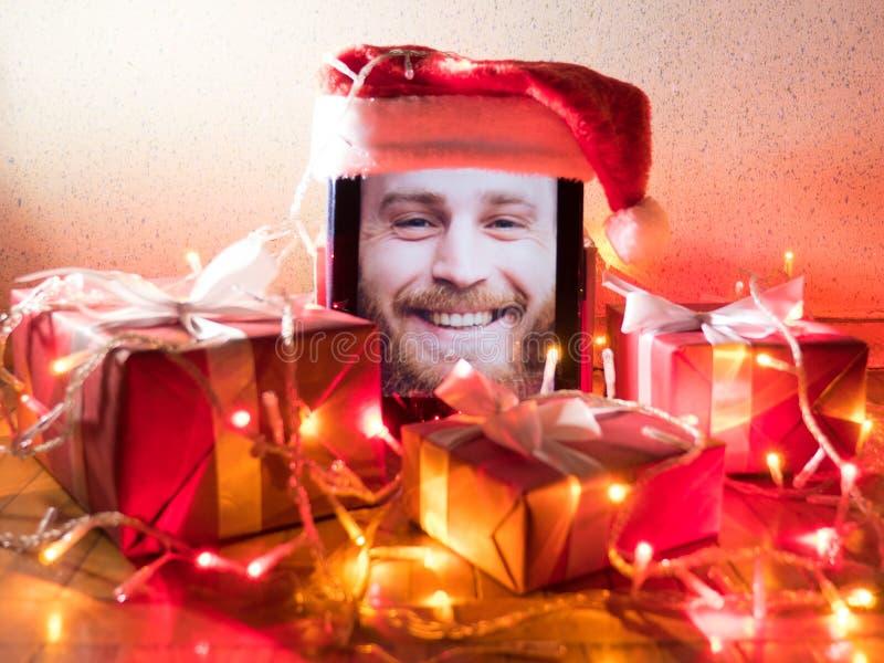 Digitale tablet met gebaard mannetje op het scherm met Kerstmis rond attributen royalty-vrije stock foto