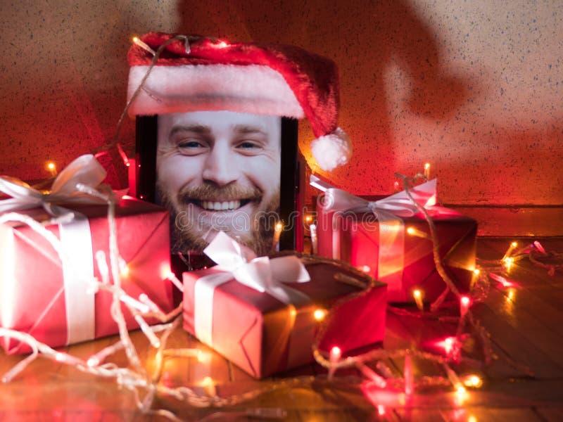 Digitale tablet met gebaard mannetje op het scherm met Kerstmis rond giften en lichten stock afbeelding