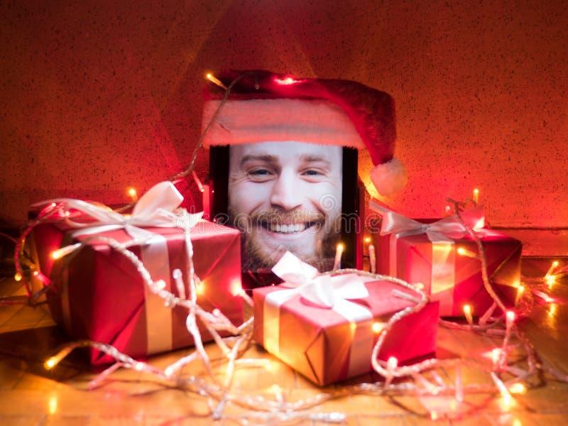 Digitale tablet met gelukkig gebaard mannetje op het scherm en santa GLB op het met Kerstmis rond attributen stock afbeeldingen