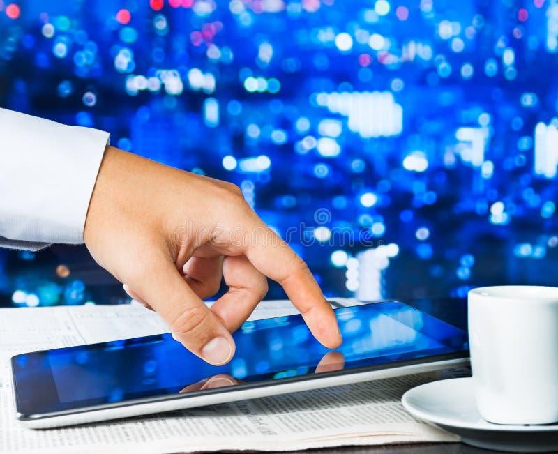 Digitale Tablette der Geschäftsmann-Note auf Wirtschaftszeitung nahe Fenster stockbild