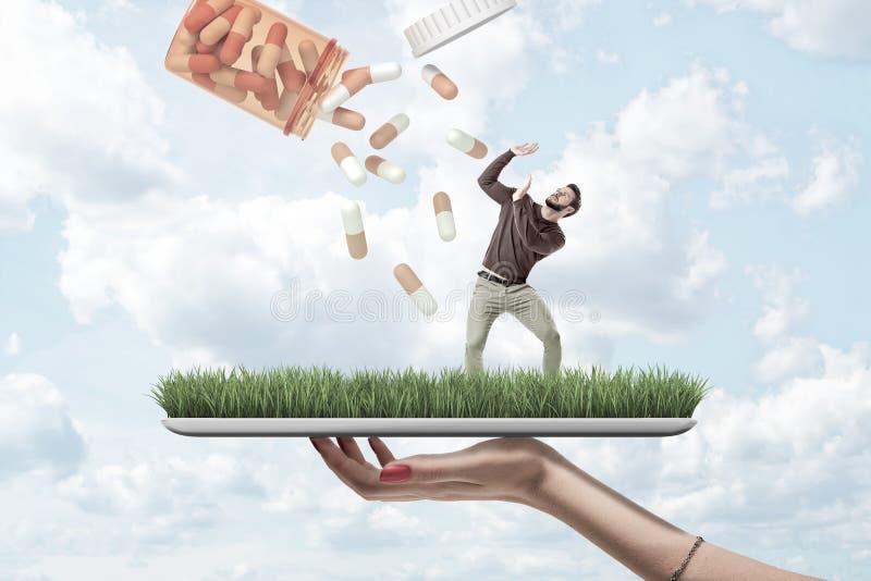 Digitale Tablette der Holding der Frau Handmit grünem Rasen auf Schirm und wenig junger Mann, der auf ihm Hände zu anhebend steht stockbild