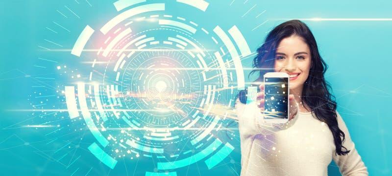 Digitale Technologie-Cirkel met jonge vrouw die een smartphone standhouden stock foto