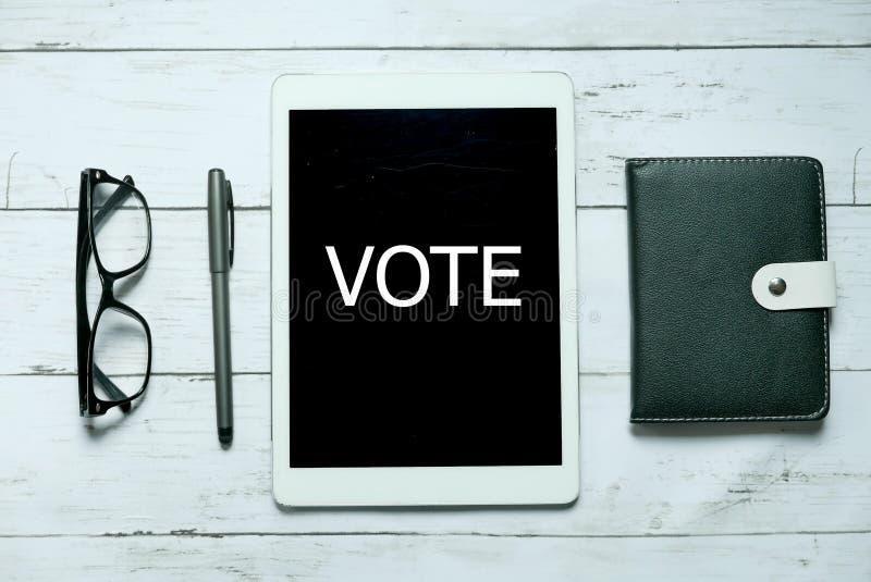 Digitales Abstimmungspolitikwahlregierungsdemokratie-Technologieon-line-konzept Draufsicht von den Gläsern, von Stift, von Notizb lizenzfreies stockfoto